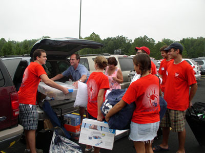 Orientation Advisors are on hand to help two parents unload the car.  Hey, where's their son in all of this?!